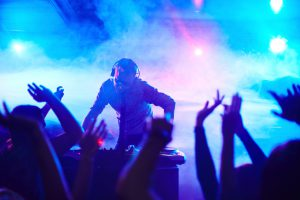 Energetic deejay standing in front of dancing people in club